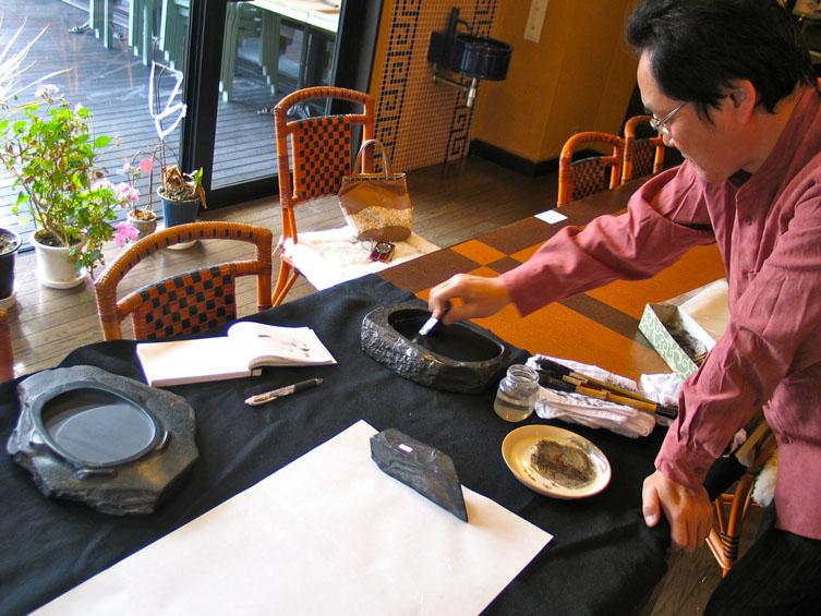 ... wrijft een inktstaaf op een inktsteen om vloeibare inkt te verkrijgen,; links de inktsteen die ik daarna getekend heb; de maker is Gyokusen. Kenshoan Suzurimuseum, Amehata, Hayakawa, Japan, 13 maart 2010