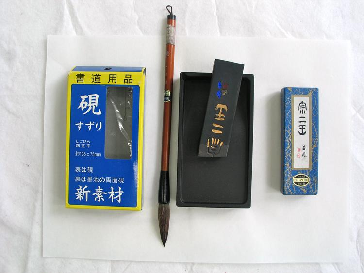 inktstaaf, inktsteen (dit is er een van plastic! gekocht in Tokyo) en penseel op een vel papier op een ondergrond van wit vilt