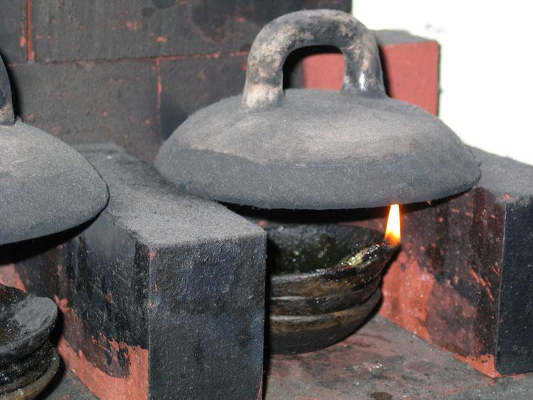 Roet is een basisbestanddeel van inkt. Met een lont wordt olie gebrand om roet te verkrijgen, die zich afzet tegen een metalen koepel boven het schaaltje olie. Boku Undo inktfabriek, Nara, Japan, 16 februari 2010