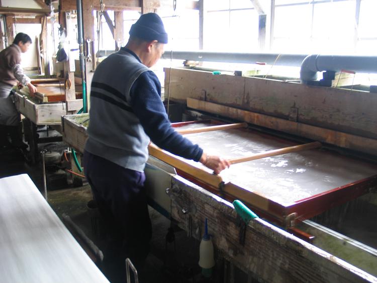 een vel papier wordt geschept in de Nishijima Washi Paper cooperative., Nakatomi, Japan, 2010