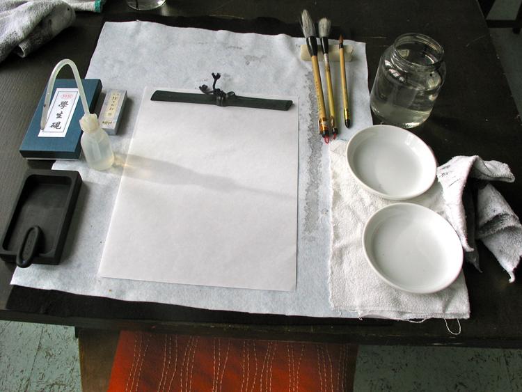 De vier vrienden liggen op wit vilt klaar voor een inkttekening. een pot water, een waterdruppelaar, schaaltjes, een penselenstandaard en lappen completeren het gezelschap. papiergewicht, ee